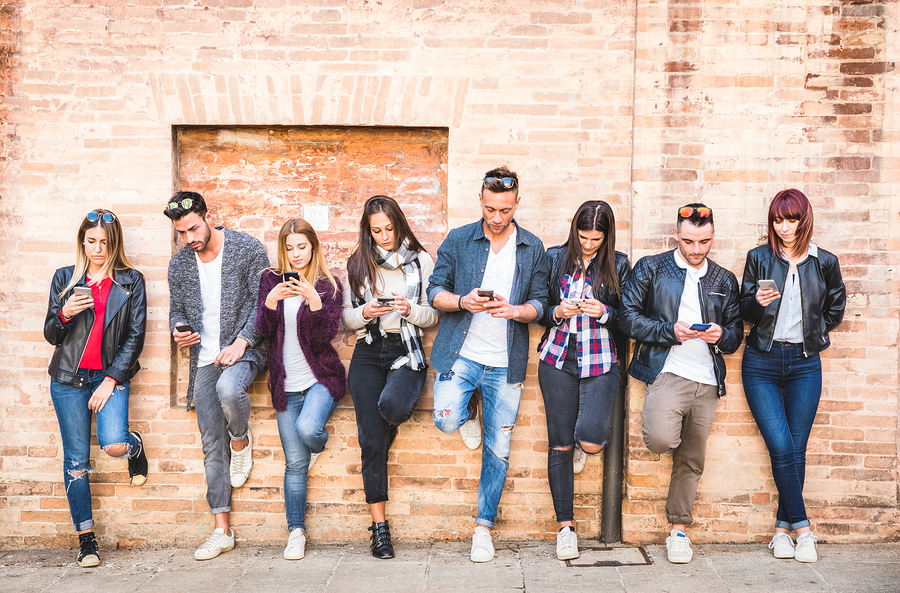 Friends group using smartphone against wall at university college backyard break - Young people addicted by mobile smart phone - Technology concept with always connected millennials - Filter image