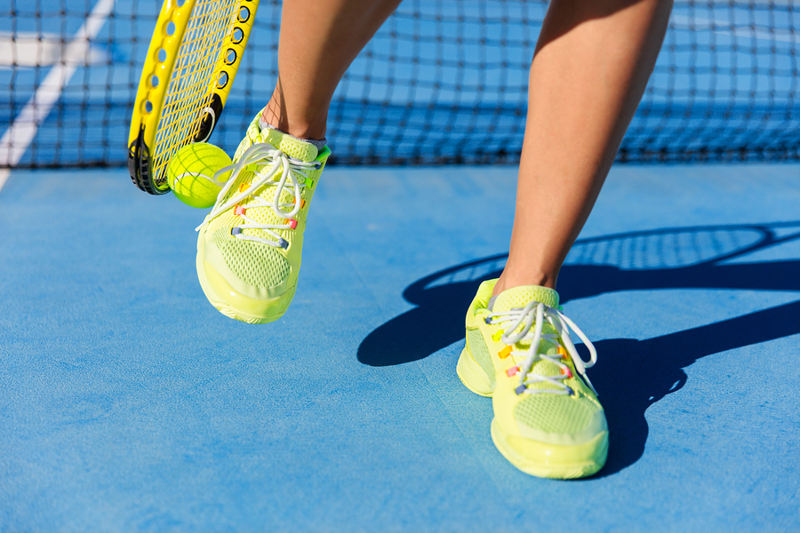 Sports athlete picking up ball with tennis racket. Female player using a technique with her running shoes to pick up during game on blue hard court. Closeup of feet, neon yellow fashion footwear.