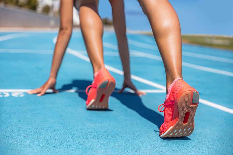 Sprinter waiting for start of race on running tracks at outdoor stadium. Sport and fitness runner woman athlete on blue run track with orange running shoes. Healthy active training.