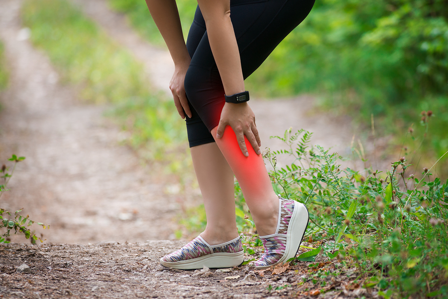 Pain in woman's shin, massage of female leg, injury while running, trauma during workout, outdoors concept