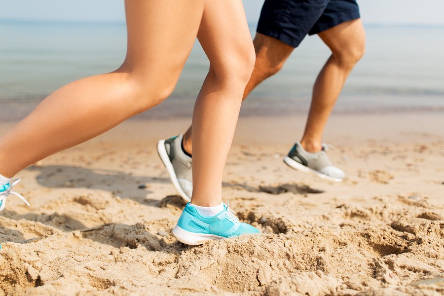 fitness, sport and technology concept - legs of couple of sportsmen in sneakers running along summer beach