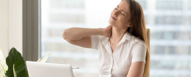 A young woman suffering from neck pain while at work.