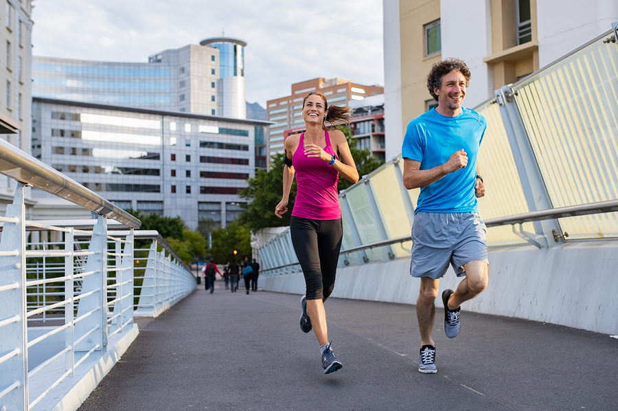 Happy man and beautiful woman jogging together city bridge. Healthy couple running on the city street. Middle aged couple running with building in the background.