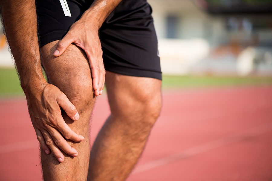 knee Injuries. young sport man with strong athletic legs holding knee with his hands in pain after suffering muscle injury during a running workout training on Running Track. Healthcare and sport concept.
