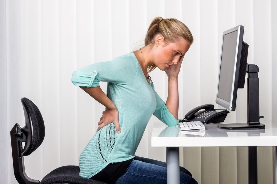 A woman sitting at a desk and experiencing back pain